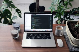 macbook pro beside white ceramic mug on brown wooden table